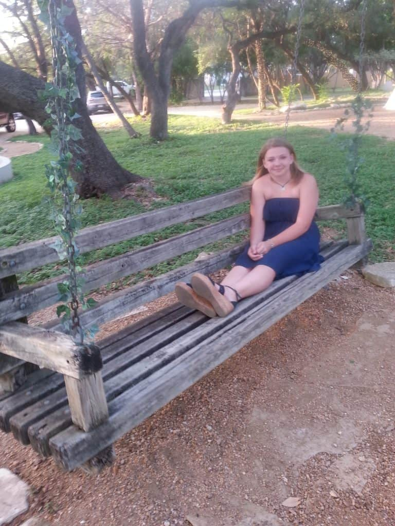 teen on an extra large porch swing