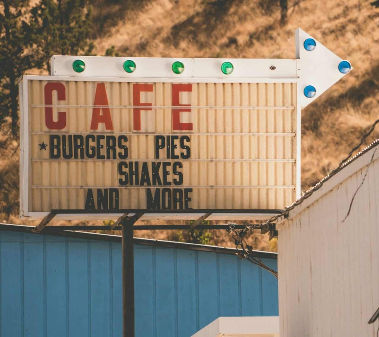 Old arrow sign with Burgers Pies Shakes and More written on it