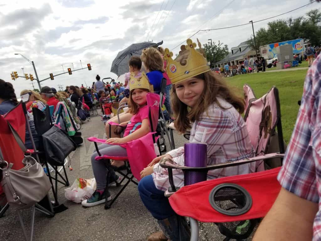 girls sitting in the crowd at the Cornyval Parade