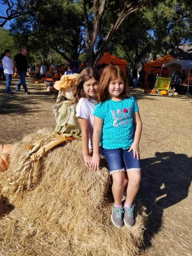 2 girls on bales of hay at the pumpkin patch